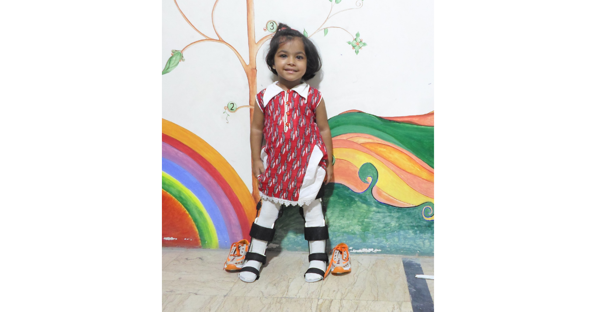Young girl smiling and standing thanks to orthotic braces